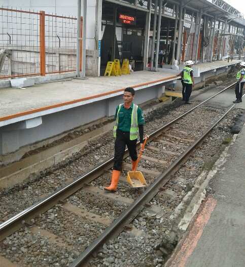 Petugas kebersihan jalur kereta di stasiun